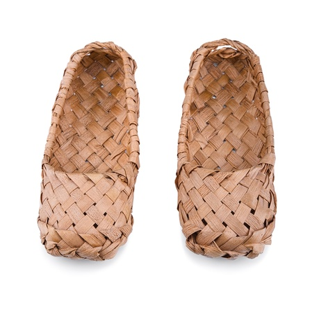 Old Russian bast shoes isolated on white background.Focus on the front. photo