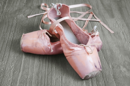 ballet slippers: Old used pink ballet shoes on wooden background