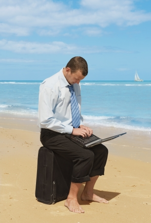 young businessman working with laptop on the beach  photo