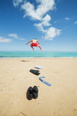 big deal: young businessman jumping on the beach after a big deal