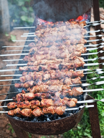 cooking shish kebab barbecue on skewers  on charcoal  outdoor dining photo