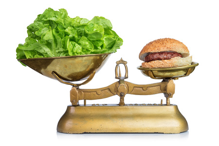 low scale: Healthy food and unhealthy food on scales.Dieting concept.Isolated.
