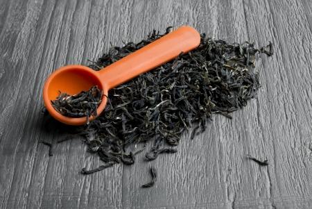 loose leaf: Pila de t� verde de hojas sueltas con la cuchara en la mesa de madera de la vendimia