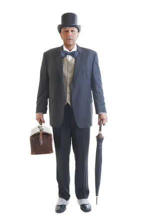 valise: Middle aged  businessman in a retro business suit with valise and umbrella isolated on white.