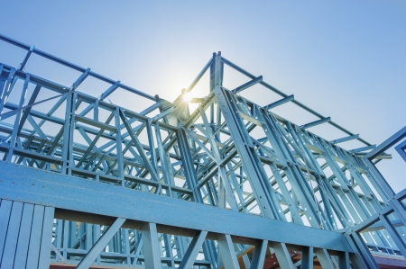 New home under construction using steel frames against a sunny sky.