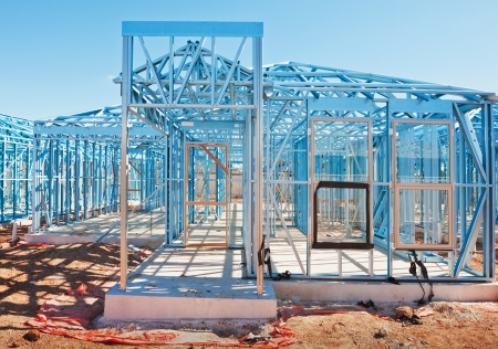 New residential construction home metal framing against a blue sky