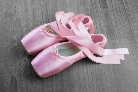 pointe: new pink ballet pointe shoes on vintage wooden background Stock Photo