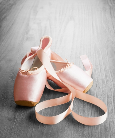classical dance: new pink ballet pointe shoes on vintage wooden background Stock Photo