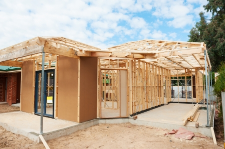 new site: New residential construction home wooden framing against a blue sky Stock Photo