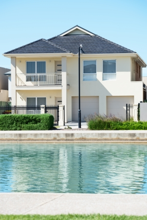 suburban: typical facade of a modern town suburban house near the pond  at noon Stock Photo