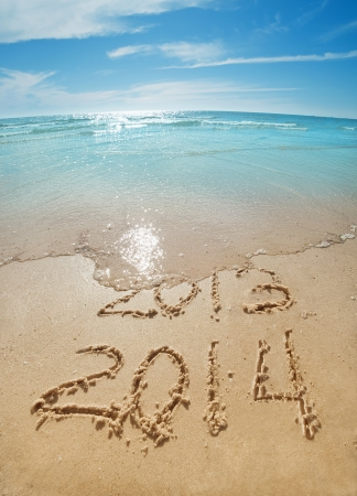 digits  2013 and 2014 on the sand seashore - concept of new year photo