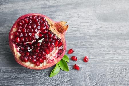 나무 빈티지 테이블 위에 달콤한 석류 열매