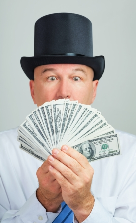 Surprised and amazed middle aged man in a retro top hat with money.Focus on the cash.  photo