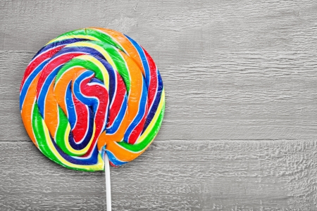Real Colorful spiral lollipop on wooden vintage table photo