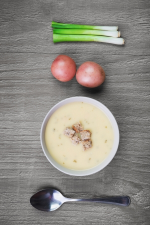 potato soup: bowl of  fresh creamy potato soup on retro wooden table