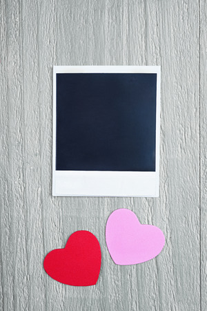 Valentines Day hearts and blank instant photo on vintage wooden background photo