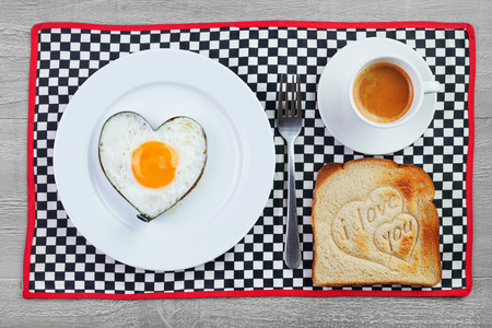 Fried egg in heart shape and toast with love message photo