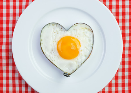 Fried egg in heart shape on vintage tablecloth photo