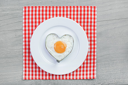 Fried egg in heart shape on vintage table photo
