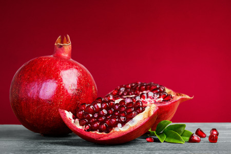 Juicy pomegranate fruit with leaves  on a red background
