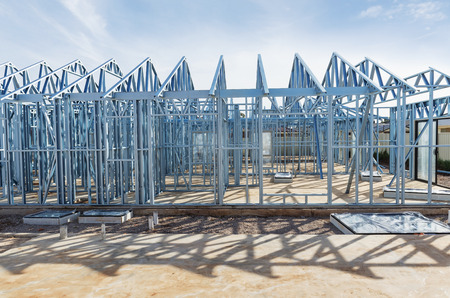 residential home: New residential construction home metal framing against a blue sky