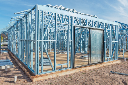 studs: New home under construction using steel frames against blue sky