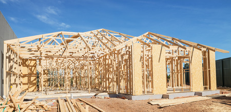 site preparation: New residential construction home framing against a blue sky.