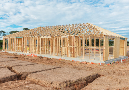 wooden joists: New residential construction home framing against a blue sky.