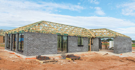 construction material: new home currently under construction against blue sky Stock Photo
