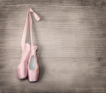 ballet clásico: Nuevos zapatos de ballet de color rosa colgando sobre fondo de madera de estilo vintage Foto de archivo