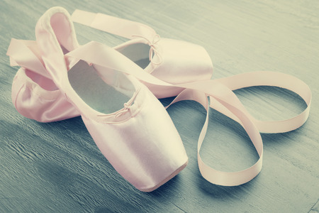pointe: new pink ballet pointe shoes on  wooden background in vintage style