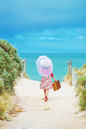 mujer con maleta: Viajero de la mujer hermosa en vestido de estilo retro en la playa de enfoque local en la mujer