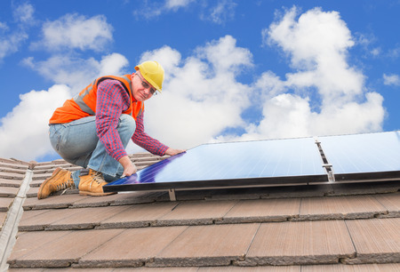 experienced worker checking solar panels on house roof