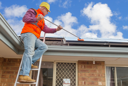 experienced worker cleaning solar panels on house roof Stockfoto