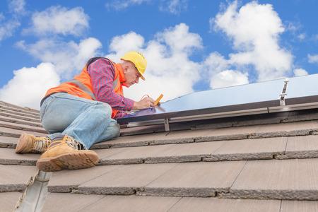 経験豊富な労働者の家の屋根にソーラー パネルをチェック
