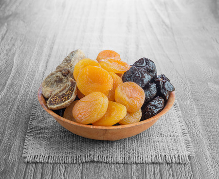 pitted: Dried pitted fruits on a wooden background  Stock Photo