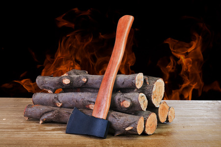 stack of firewood logs and axe on a wooden surface photo