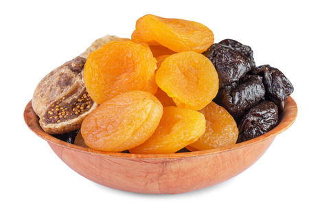 pitted: Dried pitted fruits in wooden bowl isolated on  white background