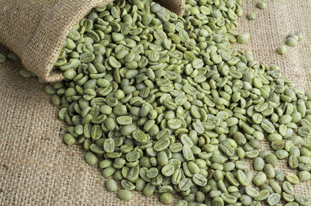 Green coffee beans in burlap sack on burlap surface Stock Photo