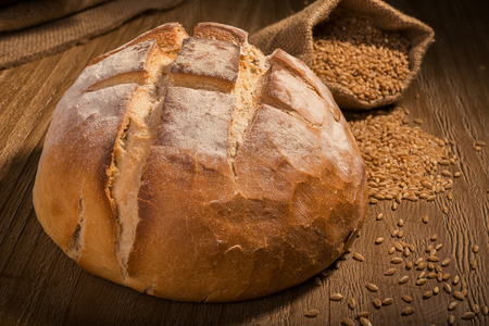 loaf of fresh homemade sour dough bread on wooden table photo