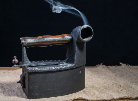 Hot Retro charcoal iron with smoke on wooden table photo