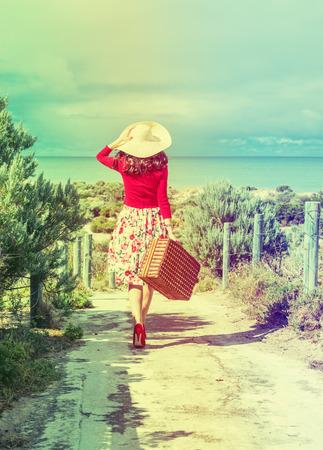 femme valise: belle dame en rouge voyageur dans le style r�tro sur la plage