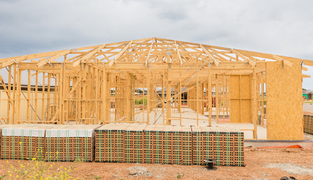 residential home: New residential construction home framing against a cloudy sky