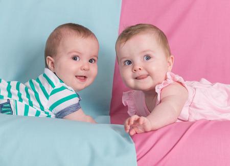 niño y niña: hermano y hermana - gemelos bebés niña y un niño en el fondo de color rosa y azul