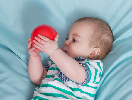 colourful ball: Adorable happy baby boy with red ball on blue background Stock Photo