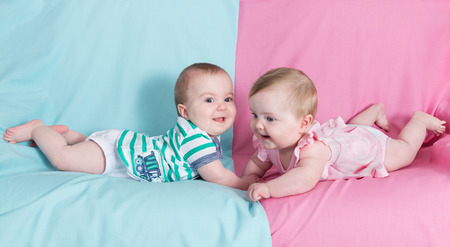 twins: brother and sister - twins babies girl and boy on pink and blue background