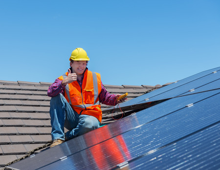 installer: young worker checking solar panels on house roof