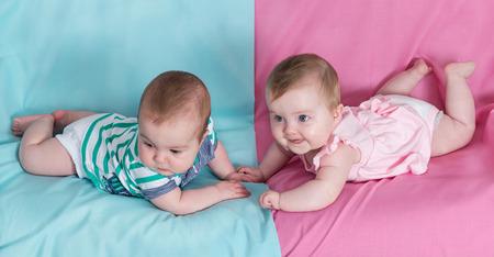 gemelos niÑo y niÑa: hermano y hermana - gemelos bebés niña y un niño en el fondo de color rosa y azul