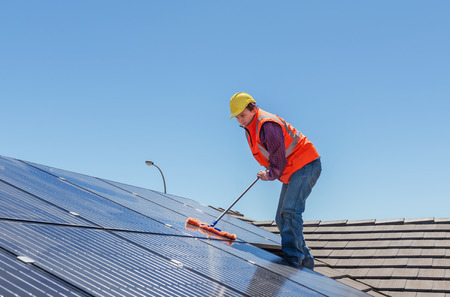 solar roof: young worker cleaning solar panels on house roof Stock Photo