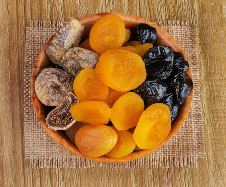 pitted: Dried pitted fruits on a wooden background